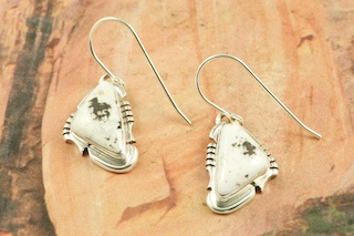 White Buffalo Turquoise set in Sterling Silver French Wire Earrings. This Beautiful Stone is formed from the minerals Calcite and Iron. It is mined near Tonopah Nevada. Created by Navajo Artist Arkie Nelson. Signed by the artist.